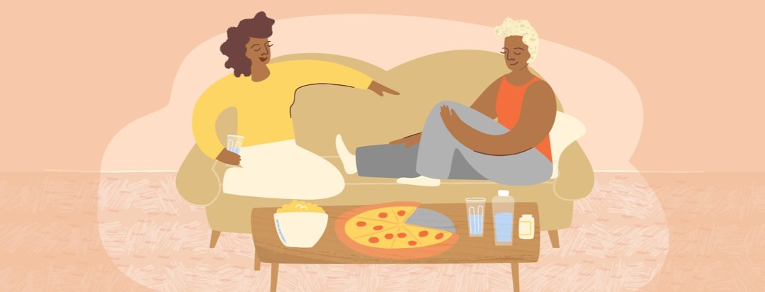 Two women sitting comfortably on a couch with pizza, snacks, and water near them